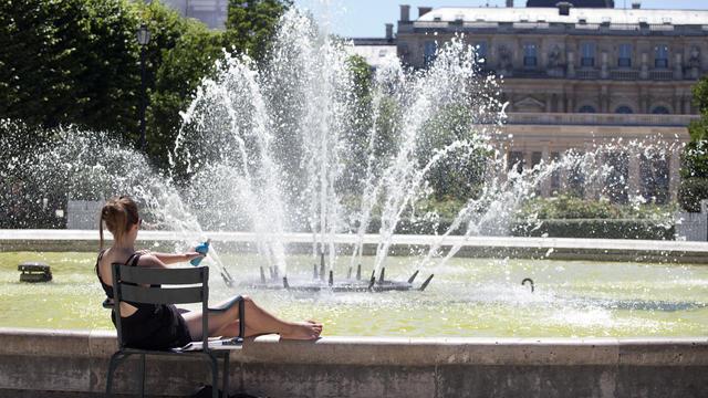 Une femme se fait bronzer au bord d'une fontaine dans les jardins du «Palais Royal» à Paris le 30 juin 2015.