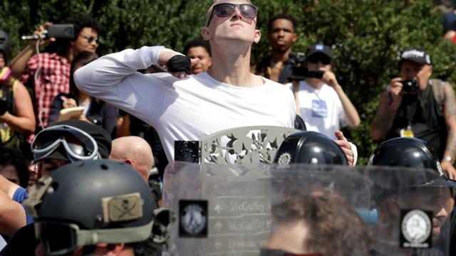 Un homme mime un égorgement alors qu'il marche dans un cortège de l'alt-right