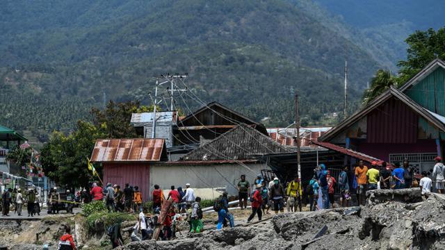 Des habitants marchent le 2 octobre 2018 au milieu des décombres dans le village de Perumnas Balaroa (Indonésie). [MOHD RASFAN / AFP]