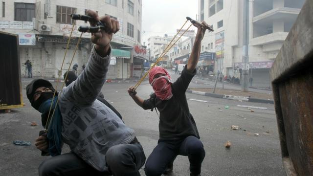 Des Palestiniens armés de fronde à Hébron le 29 octobre 2015 [HAZEM BADER / AFP]