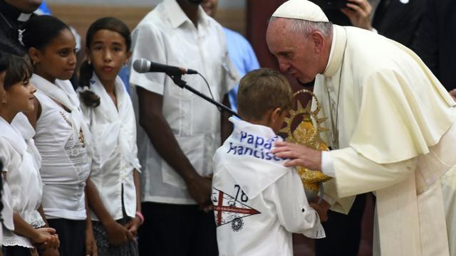 """Le pape François entouré d'enfants le 21 septembre 2015 dans le dans le sanctuaire de la Vierge de la charité """"del Cobre"""" à Santiago de Cuba [FILIPPO MONTEFORTE / POOL/AFP]"""