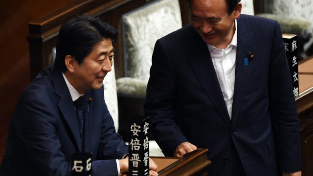 Le Premier ministre japonais, Shinzo Abe (G) et son chef de cabinet Yoshihide Suga (D), le 18 septembre 2015 [TOSHIFUMI KITAMURA / AFP]