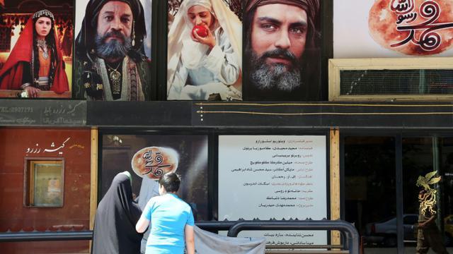 """Des Iraniens devant un cinéma passant la première projection de """"Mahomet"""", le film le plus cher de l'histoire du cinéma iranien consacré à l'enfance du prophète, le 27 août 2015 à Téhéran [ATTA KENARE / AFP]"""