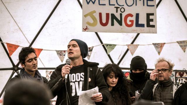 """Jude Law (au micro) dans un théâtre informel de la """"jungle"""" de Calais, le 21 février 2016 [PHILIPPE HUGUEN / AFP/Archives]"""