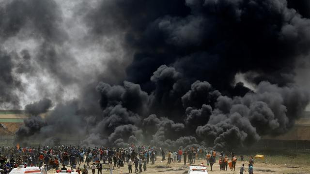 Des manifestants palestiniens brûlent pneus face à la barrière de sécurité entre Israël et la bande de Gaza, lors de nouvelles protestations à l'est de Jabaliya, le 13 avril 2018  [MOHAMMED ABED / AFP]
