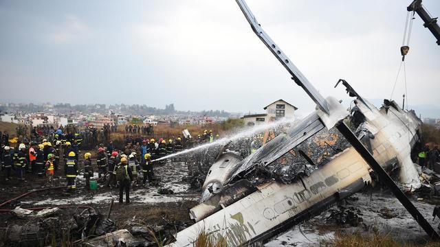 Des secours népalais rassemblés autour de la carcasse d'avion fumante, le 12 mars dernier.