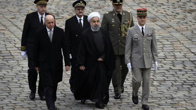 Le président iranien Hassan Rohani (c), le ministre français des Affaires étrangères Laurent Fabius, lors d'une cérémonie aux Invalides, le 28 janvier 2016 à Paris [LIONEL BONAVENTURE / AFP]