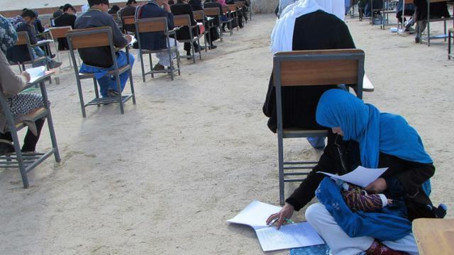 Cette photographie devenue virale en Afghanistan, obtenue depuis le compte Facebook du professeur afghan Yahya Erfan et prise le 16 mars 2018, montre Jahantab Ahmadi passant un examen d'entrée à l'université assise par terre avec son bébé [Yahya Erfan / Yahya Erfan/AFP]