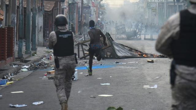 Des policiers face à des manifestants, le 12 février 2019 à Port-au-Prince [HECTOR RETAMAL / AFP]