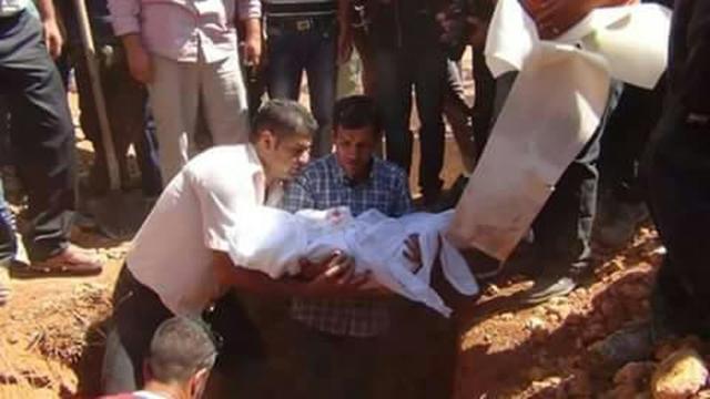 Le père du petit Aylan Kurdi (c) tient entre ses bras la dépouille de son fils avant son enterrement à Kobané en Syrie, le 4 septembre 2015 [STR / AFP]