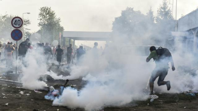Des réfugiés courent pour se protéger des gaz lacrymogènes à la frontière serbo-croate près de la ville de Horgos, le 16 septembre 2015 [ARMEND NIMANI / AFP]