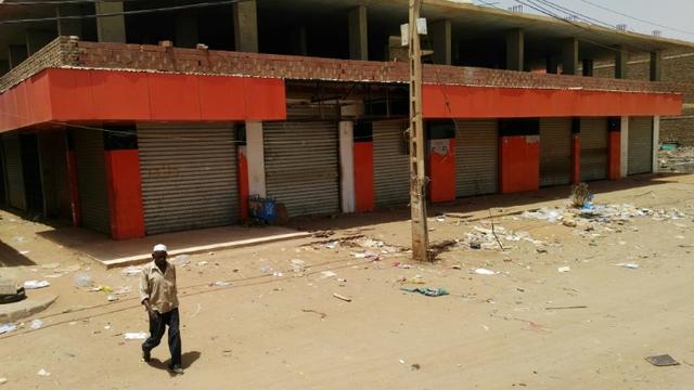Un Soudanais marche devant des magasins fermés dans une rue déserte de la capitale Khartoum, le 10 juin 2019.