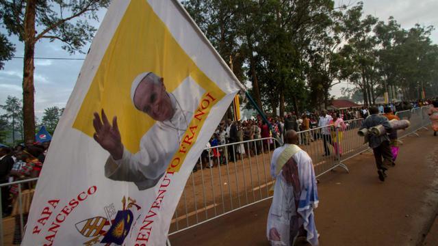 Un homme tient une bannière à l'effigie du pape François à Namugongo, en Ouganda, le 28 novembre 2015 [ISAAC KASAMANI / AFP]