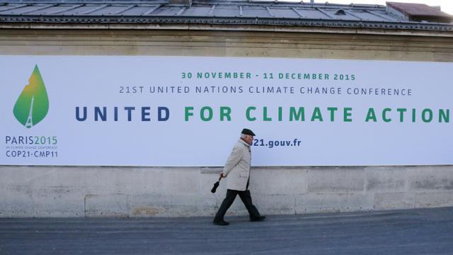 Un homme passe devant un panneau annonçant la tenue de la conférence de Paris (COP 21) sur le climat, le 14 janvier 2015 [Jacques DEMARTHON / AFP/Archives]