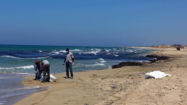 Des hommes enlèvent la dépouille d'un migrant échoué sur une plage libyenne à 60km à l'est de Tripoli, le 19 juillet 2014 [Mahmud Turkia / AFP]