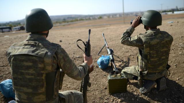Un soldat turc surveille à l'aide de jumelles la frontière avec le nord de la Syrie, près de Mursitpinar, depuis la ville de Suruc, le 4 octobre 2014 [BULENT KILIC / AFP/Archives]