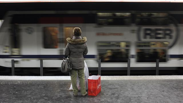 Une femme attend un RER à Paris [Fred Dufour / AFP/Archives]