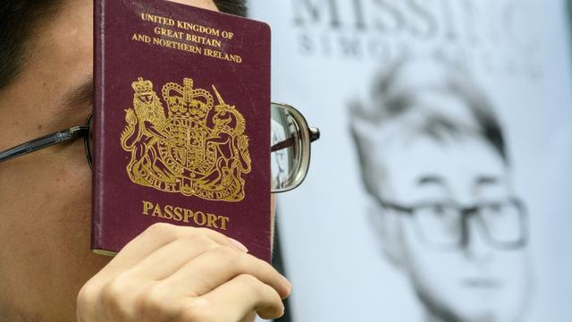 Un militant brandit un passeport britannique devant un portrait de Simon Cheng, le 21 août 2019 devant le consulat de Grande-Bretagne à Hong Kong [Anthony WALLACE / AFP/Archives]