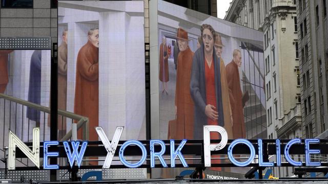 """Le département de la police de New York, à la station de métro de Times Square, à Manhattan surplombée par une reproduction de l'oeuvre de  George Tooker intitulée """"The Subway, 1950"""", le 4 août 2014 [Timothy A. Clary / AFP/Archives]"""