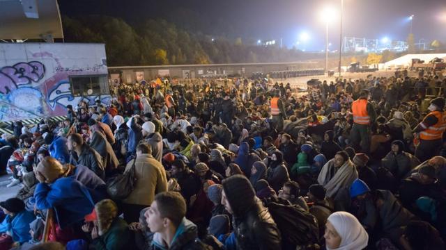Migrants et réfugiés attendent de monter dans un bus le 23 octobre 2015 à Sentilj à la frontière entre la Slovénie et l'Autriche [Rene Gomolj / AFP]