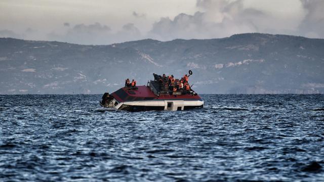 Des migrants et réfugiés appellent à l'aide alors que leur bateau est en train de couler près des côtes de l'île grecque de Lesbos, le 30 octobre 2015 en mer Egée [ARIS MESSINIS / AFP]