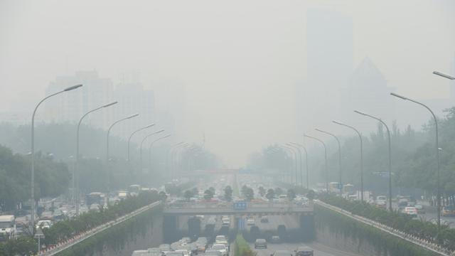 Des véhicules lors d'un jour de brouillard à Pékin, le 23 juin 2015 [Str / AFP/Archives]