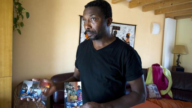 Amadou Ouedraogo pose avec des photos de son frère et de la famille de ce dernier, qui se trouvaient à bord de l'avion qui s'est écrasé au Mali, le 25 juillet 2014 à Remouille, près de Nantes [Jean-Sebastien Evrard / AFP/Archives]