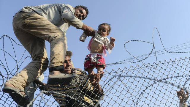 Photo prise le 14 juin 2015 par le photographe de l'AFP Bülent Kiliç, récompensé du Visa d'Or News à Perpignan, montrant  un enfant syrien fuyant la guerre porté à bout de bras de l'autre côté de des barbelés en territoire turc au point de passage d'Akcakale dans la province de Sanliurfa  [BULENT KILIC / AFP]