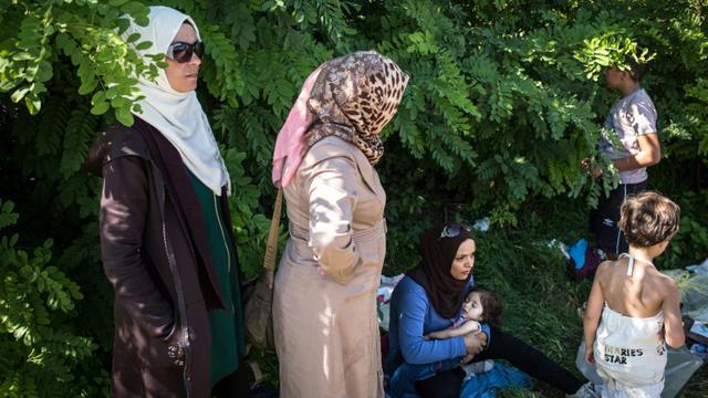Des femmes attendent à Bapska en Croatie à la frontière avec la Serbie, le 23 septembre de monter dans des autobus pour les conduire dans un centre de transit [FEDERICO SCOPPA / AFP]