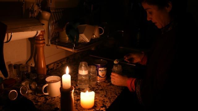 Une femme allume des bougies chez elle à Montevideo le 16 juin 2019 lors d'une panne d'électricité [MIGUEL ROJO / AFP]