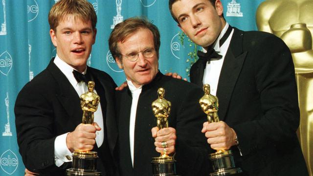 """Les acteurs et scénaristes Matt Damon (gauche) et Ben Affleck (droite) posent avec Robin Williams (centre) et leurs Oscars pour """"Will Hunting"""" le 23 mars 1998 à Los Angeles [Hal Garb / AFP/Archives]"""