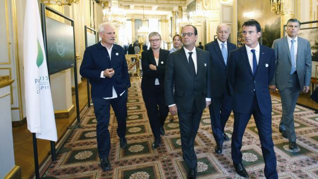 Le présient français Francois Hollande (C) et son Premier ministre Manuel Valls (D) avec le photographe Yann Arthus-Bertrand (G) avant l'ouverture de la Cop 21, au palais de l'Elysée, à Paris, le 10 septembre 2015 [Charles PLATIAU / POOL/AFP]