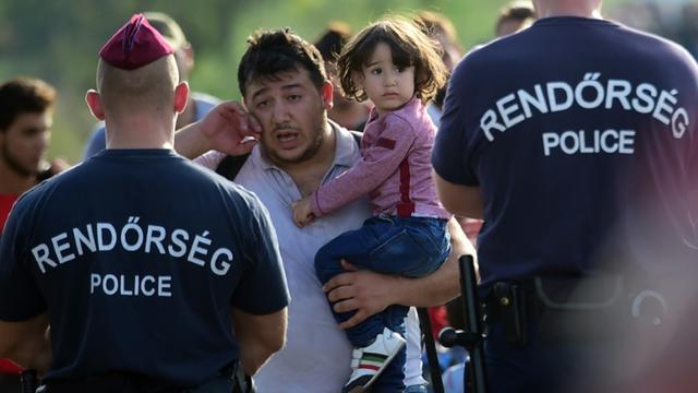Bloqué par des policiers hongrois,un migrant essuie ses larmes le 14 septembre 2015 près de Roszke à la frontière entre la Hongrie et la Serbie [ATTILA KISBENEDEK / AFP]