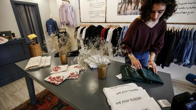 Des T-shirts de la ligne de vêtements lancée par Yasmeen Mjalli, dans la boutique de Ramallah le 19 décembre 2018 [ABBAS MOMANI / AFP]