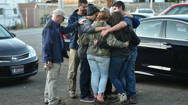 Des personnes prient lors d'une veillée en mémoire des victimes du tueur de Roseburg à Winston, dans l'Oregon, le 3 octobre 2015 [Josh Edelson / AFP]