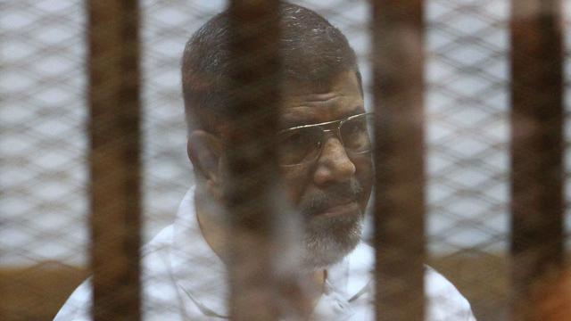 Le président islamiste Mohamed Morsi  destitué par l'armée, derrière les grillages du banc des accusés lors de son procès au Caire le 18 août 2014 [ / AFP/Archives]
