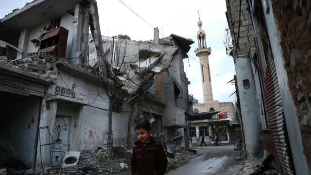 Un enfant marche dans une rue bordée de maisons détruites, le 9 janvier 2017 à Douma, près de Damas, en Syrie [Abd Doumany / AFP]