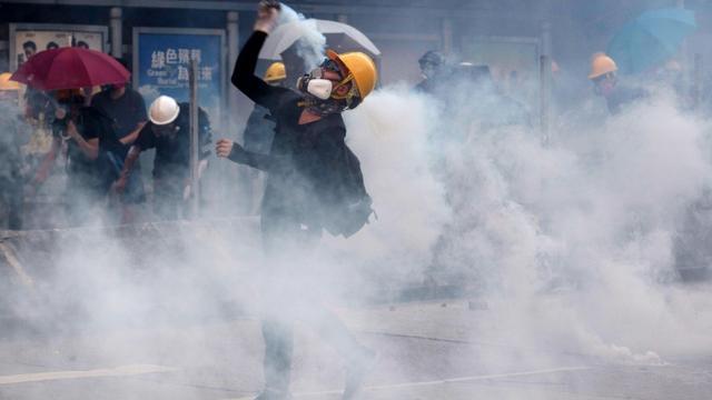 Un manifestant renvoie vers les forces de l'ordre une canette de gaz lacrymogène, le 5 août 2019 à Hong Kong [Isaac LAWRENCE / AFP/Archives]