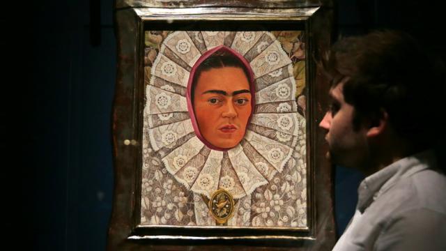 Un employé du musée Victoria & Albert Museum de Londres devant un autoportrait de Frida Kahlo lors d'une exposition consacrée à l'artiste mexicaine, le 13 juin 2018 [Daniel LEAL-OLIVAS / AFP]