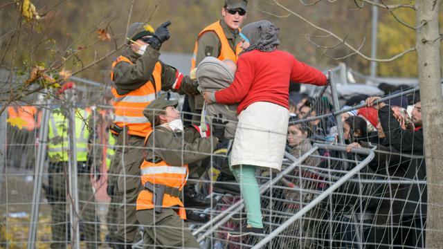 Des militaires autrichiens empêchent une femme tenant son bébé dans les bras de passer un grillage alors qu'elle tente de traverser la frontière austro-slovène depuis Sentilj, en Slovénie, le 30 octobre 2015 [Rene Gomolj / AFP]