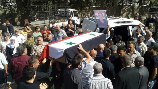 Photo diffusée par l'agence de presse officielle syrienne Sana montrant des hommes transportant le cercueil de l'une des victimes des attaques commises le 25 juillet 2018 par le groupe jihadiste Etat islamique (EI), lors de funérailles le 26 juillet 2018 dans la ville de Soueida, dans le sud de la Syrie [STR / SANA/AFP]