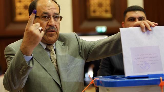 IL'ex-Premier ministre Nouri al-Maliki montre son doigt taché d'encre après avoir voté aux élections parlementaires à Bagdad, le 30 avril 2014 [Ali al-Saadi / AFP/Archives]