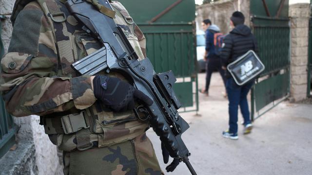 """Un militaire de garde devant l'entrée de l'école """"La Source"""" le 12 janvier 2016 à Marseille [BORIS HORVAT / AFP]"""
