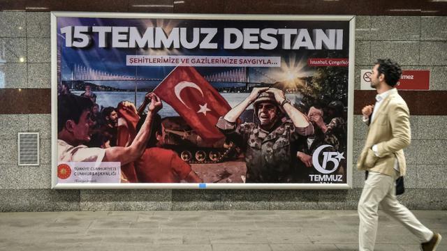 """Un homme passe devant une affiche """"La légende du 15 juillet"""", le 14 juillet 2017, à la veille de l'anniversaire de la tentative de coup d'Etat en Turquie. [OZAN KOSE / AFP]"""