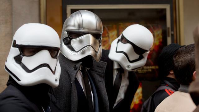 """Des fans costumés en """"Stormtroopers"""" font la queue devant le Grand Rex pour voir le dernier opus """"Star Wars"""", le 16 décembre 2015 à Paris [ALAIN JOCARD / AFP]"""