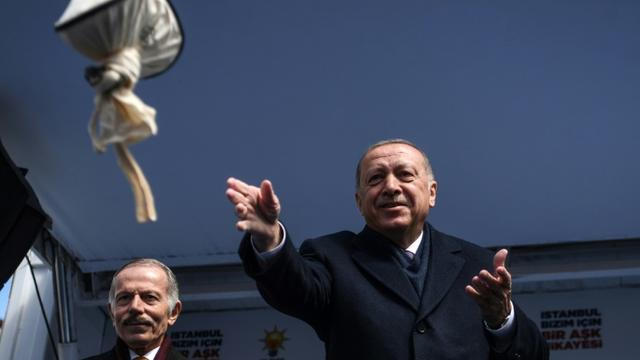 Le président turc Recep Tayyip Erdogan lance un sac de thé noir à ses partisans lors d'un meeting électoral pour les municipales, le 30 mars 2019 à Istanbul [Ozan KOSE / AFP]