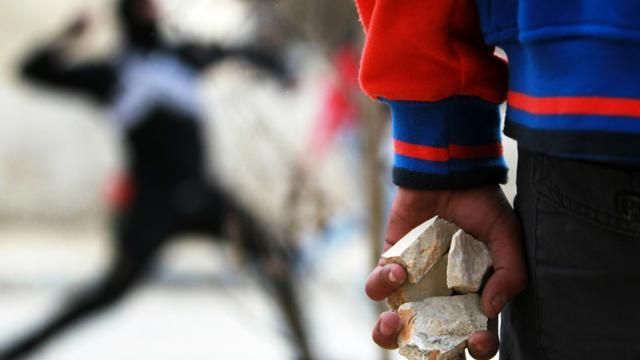 Un Palestinien tient des pierres dans ses mains lors d'affrontements avec des soldats israéliens, le 13 février 2015, près de Bethléem. [Musa AL-SHAER / AFP/Archives]