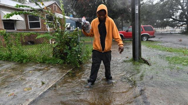 Un habitant de Jacksonville marche dans une rue inondée, après le passage de l'ouragan Matthew, le 7 octobre 2016 en Floride [JEWEL SAMAD / AFP]