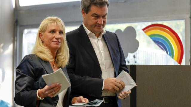 Markus Soeder, ministre-président de Bavière, membre de l'Union chrétienne-sociale (CSU), vote aux élections régionales avec sa femme Karin Soeder à Nuremberg, le 14 octobre 2018 [Odd ANDERSEN / AFP]