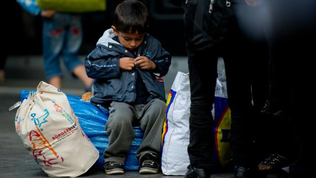 Un garçonnet attend à la gare centrale de Munich avec des milliers d'autres migrants tout juste arrivés d'Autriche d'être dirigés vers des centres d'accueil, le 5 septembre 2015 [SVEN HOPPE / DPA/AFP]